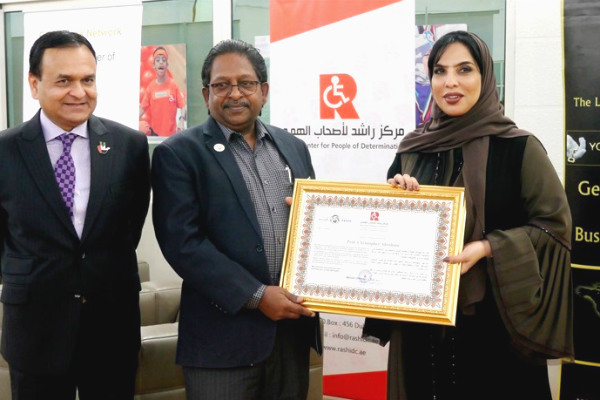 Prof. Christopher Abraham, Professor and Head of Campus (Dubai) at SP Jain School of Global Management, (centre) receives a token of appreciation from Her Excellency Ms. Mariam Othman, Founder and CEO of Rashid Centre for people of determination (right) in the presence of Dr. Tariq Nizami, Founder & CEO of CEO Clubs Network (left)